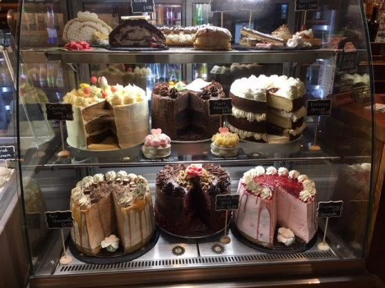 Three tiers of cakes on display at a cafe